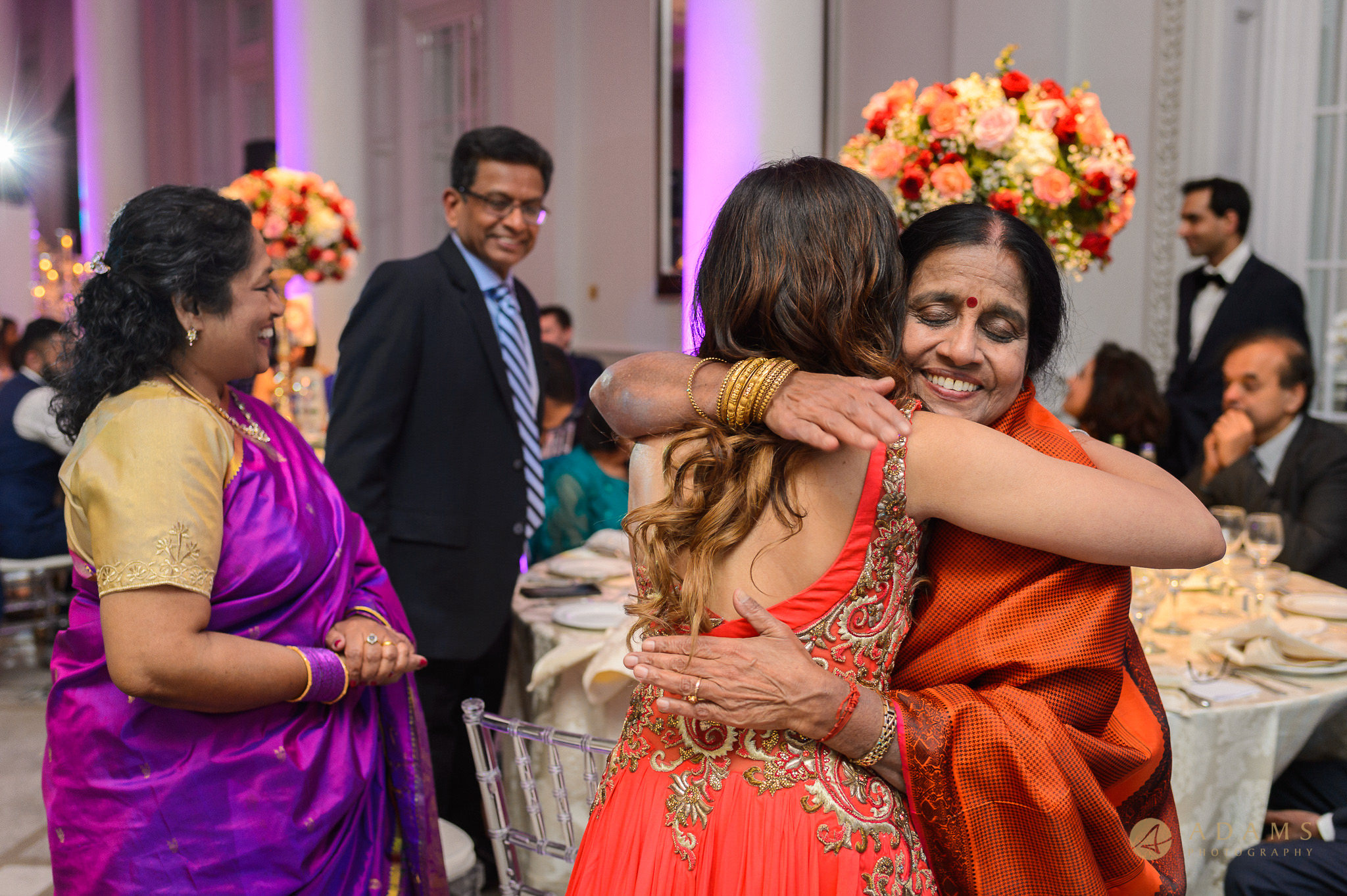 Mother of the groom is hugging the bride