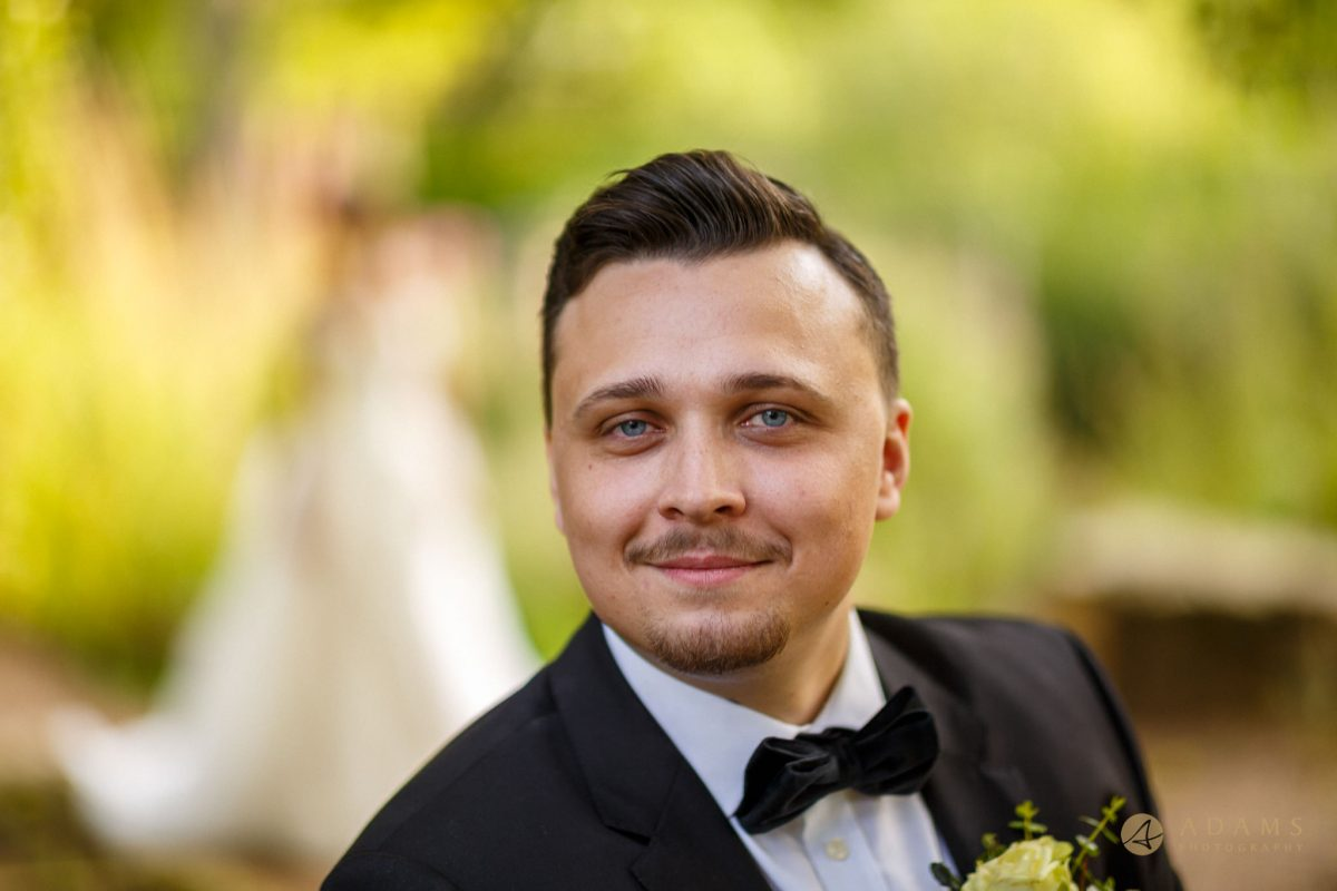 Portrait of the groom with the bride in the background
