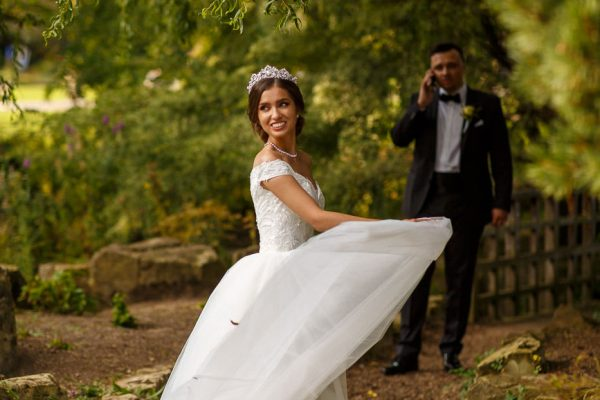 Bride posing while groom on the phone