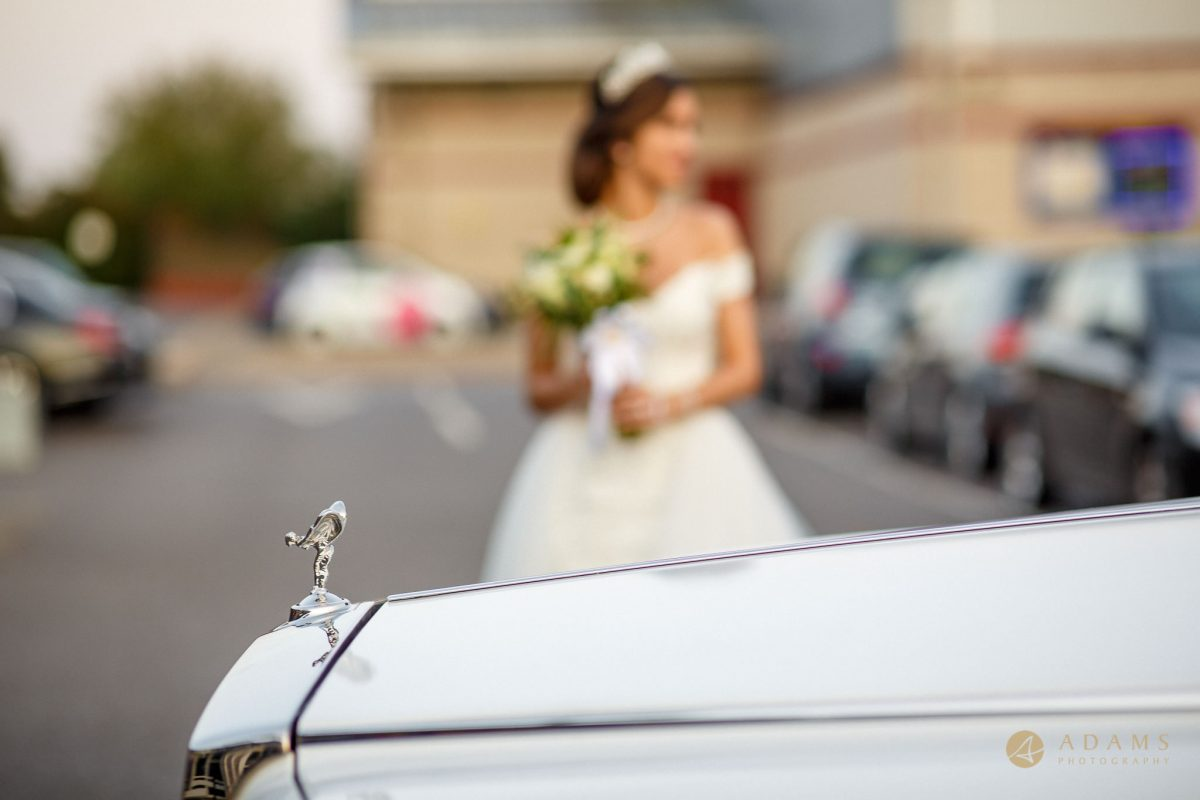 Bride by the wedding car