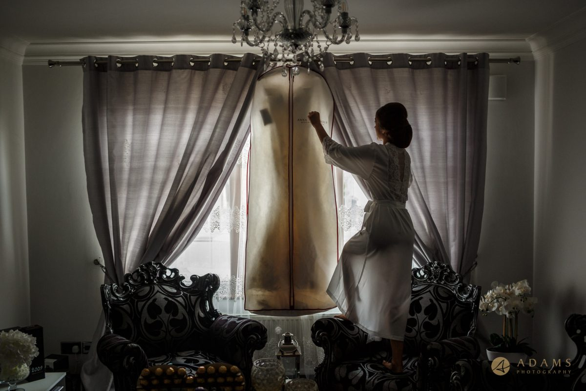 Old-Marylebone Town Hall Wedding Photography bride is hangin her wedding dress at the window
