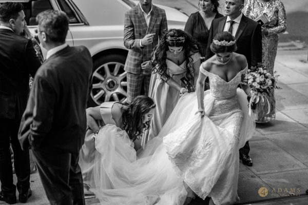 Bride folding her dress beforeing going up the stairs at Old-Marylebone Town Hall