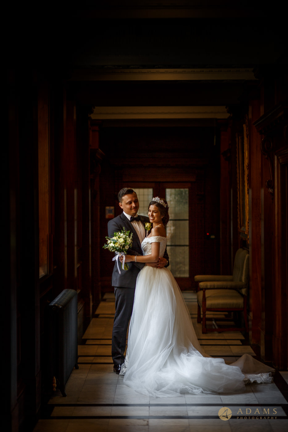 Bride and groom posing for their photo in the hall