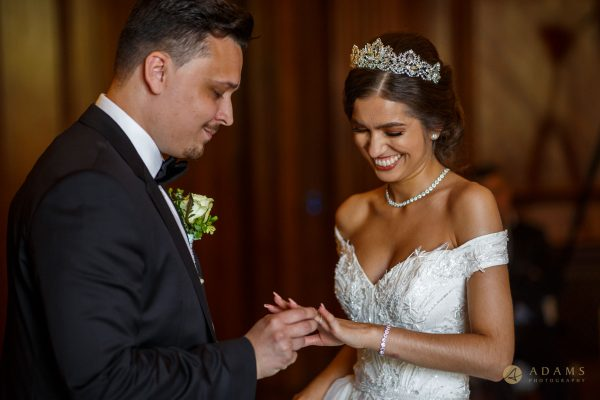 Groom putting a ring on the bride