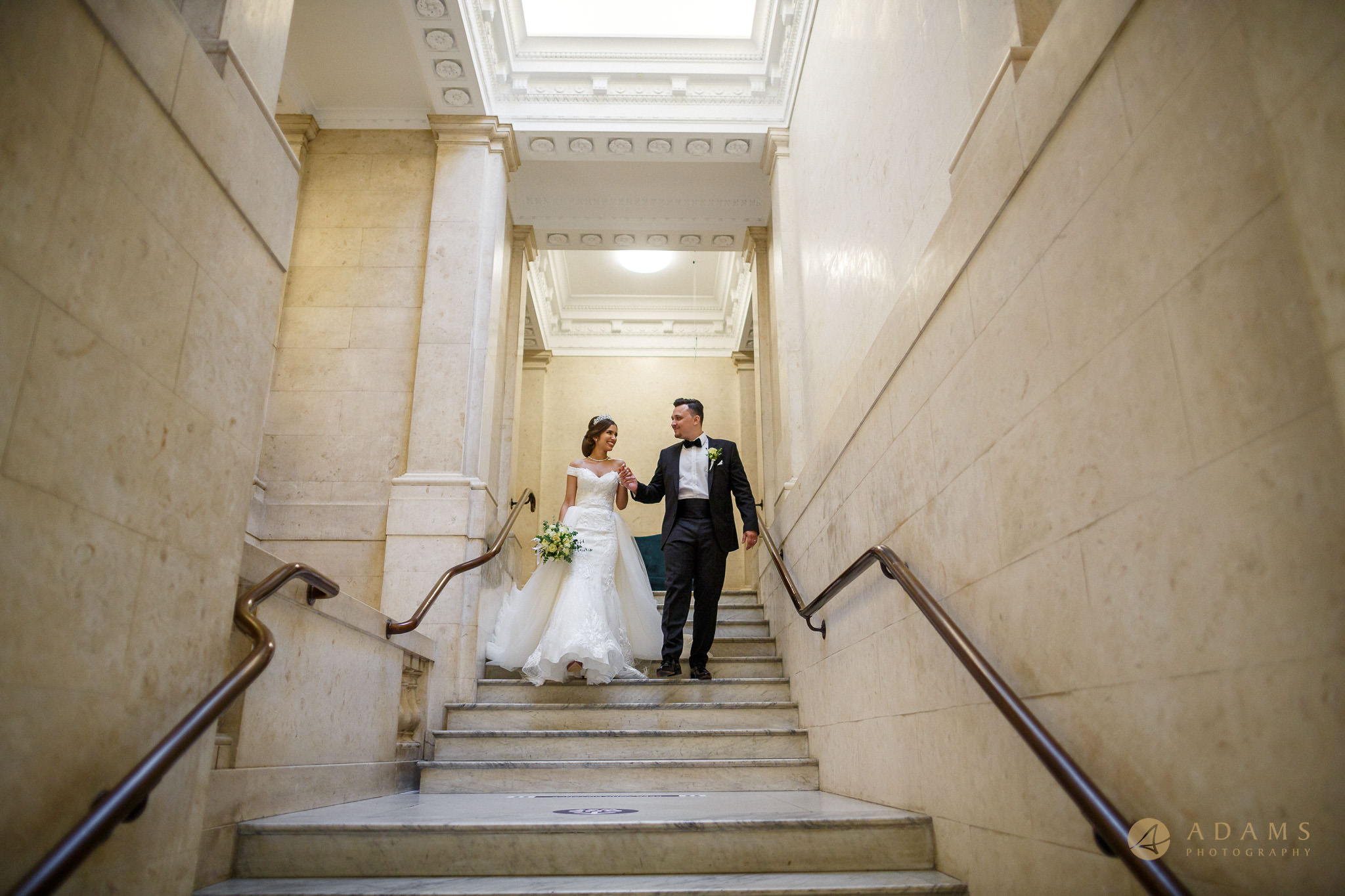 Bride and groom walking down the starts at Old Marylebone Town Hall