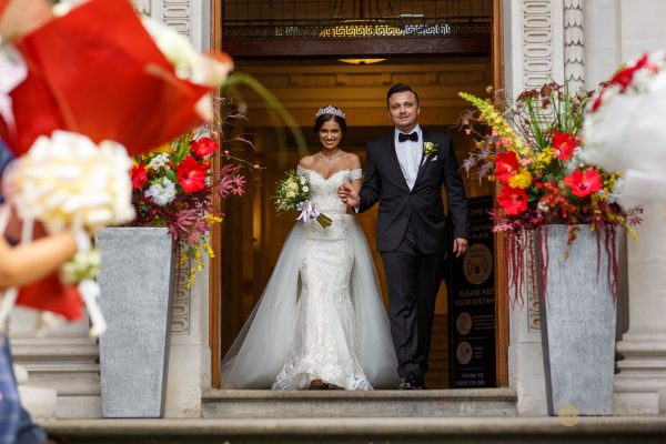 Bride and groom exit bu the main doors at the Old Marylebone Town Hall