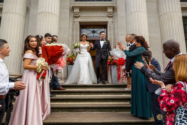 Bride and groom and the guests on the staircase