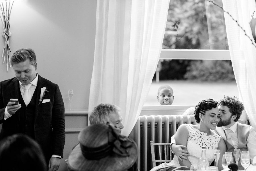 couple kissing during the wedding speeches