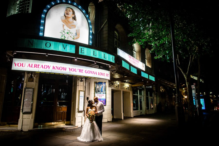 Couple posing in front of Waldorf Astoria Hotel in London after the wedding
