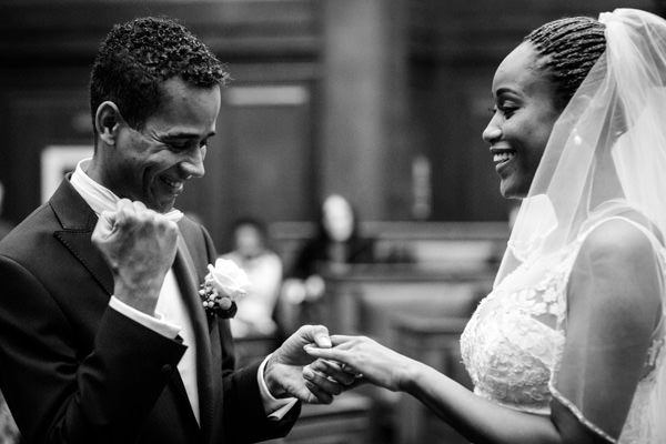 Groom and Bride during their ceremony, groom excited with his fist up after his put a ring on brides hand