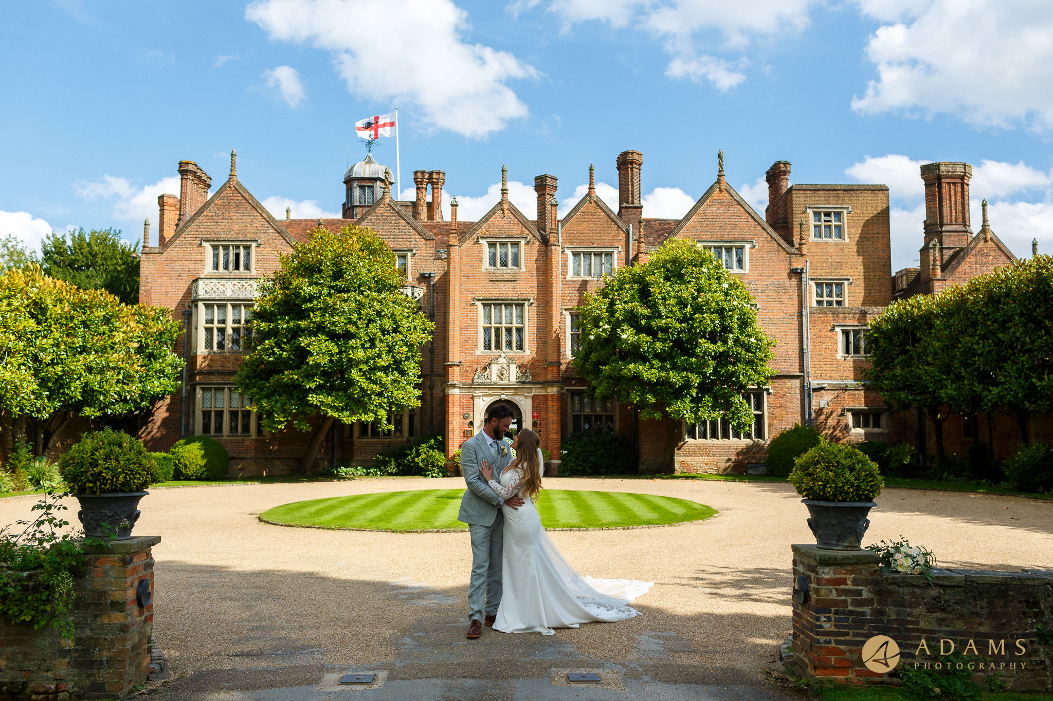 Married couple posing in front of the Great Fosters Hotel