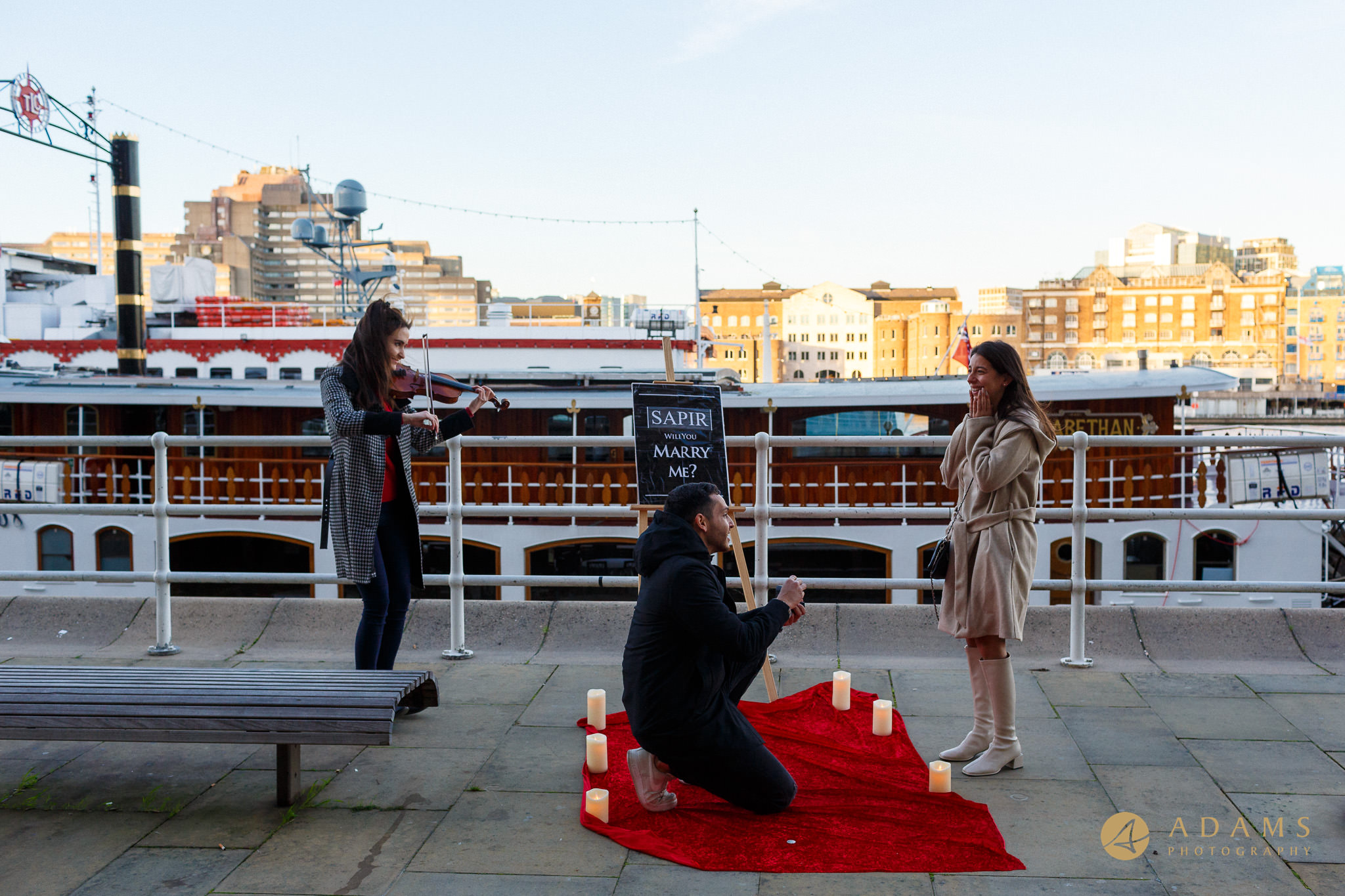 proposing on the knee by Tower Bridge